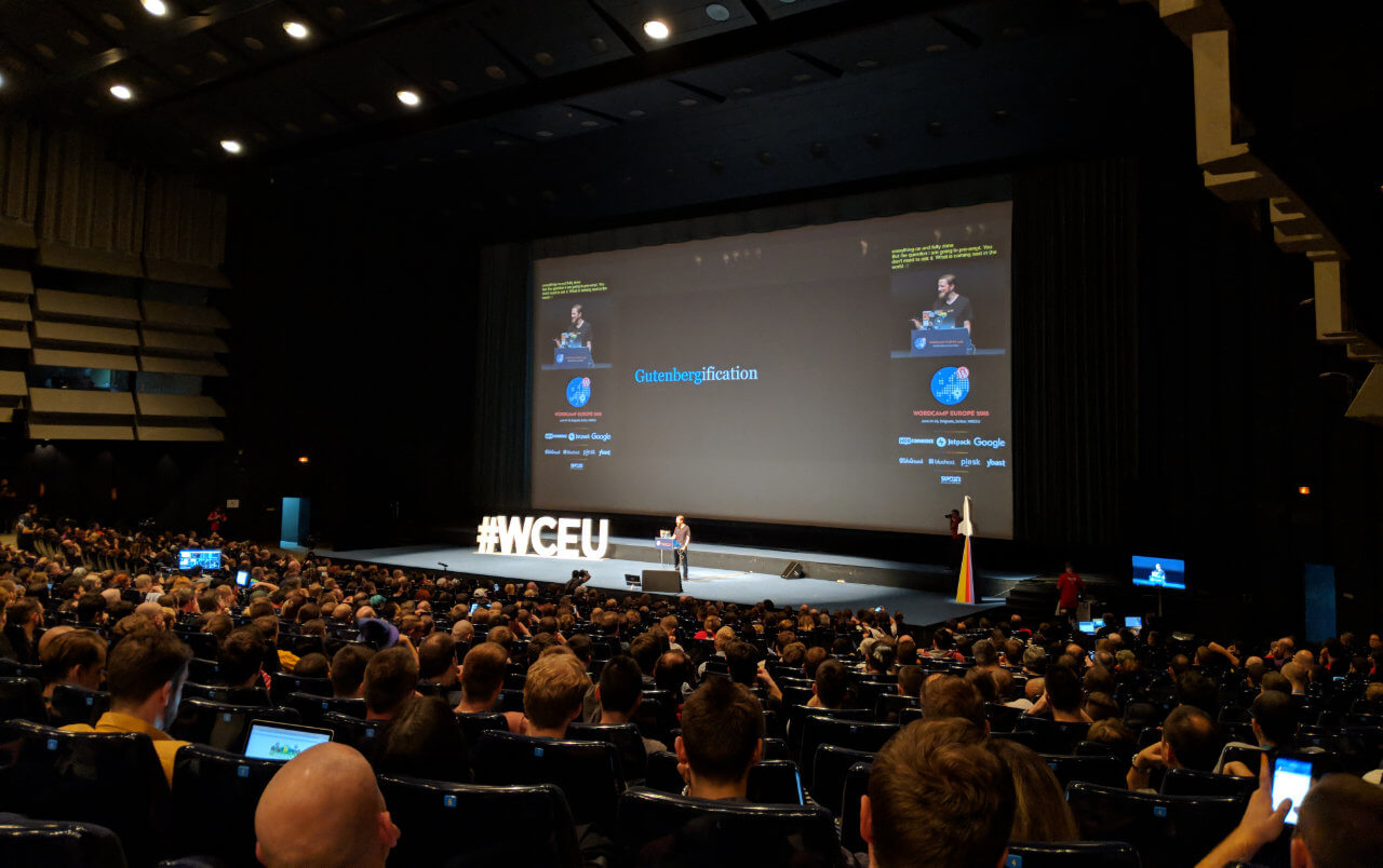 A person on stage delivering a talk at WordCamp Europe about WordPress Gutenberg.